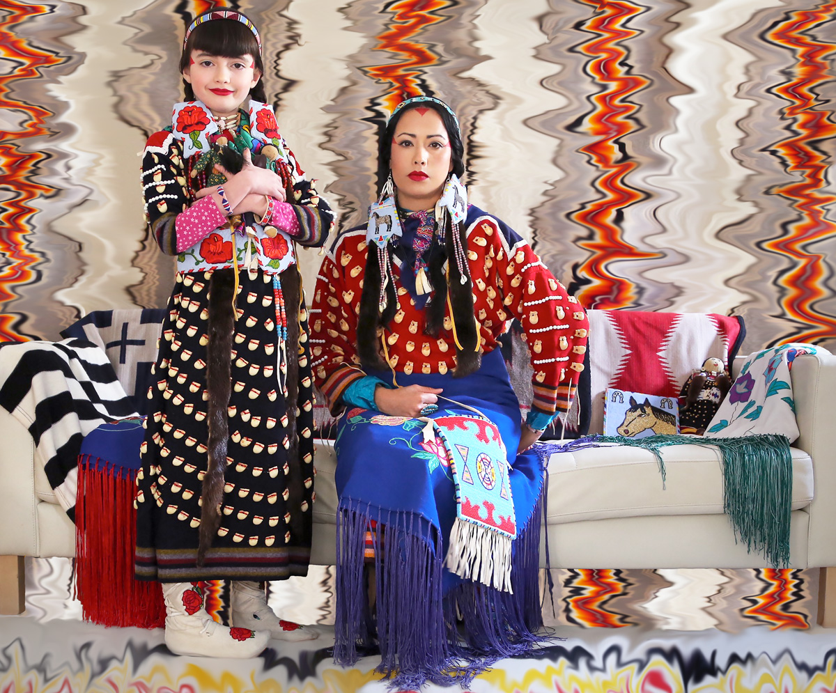 a woman and her daughter sitting on a couch in traditional clothing
