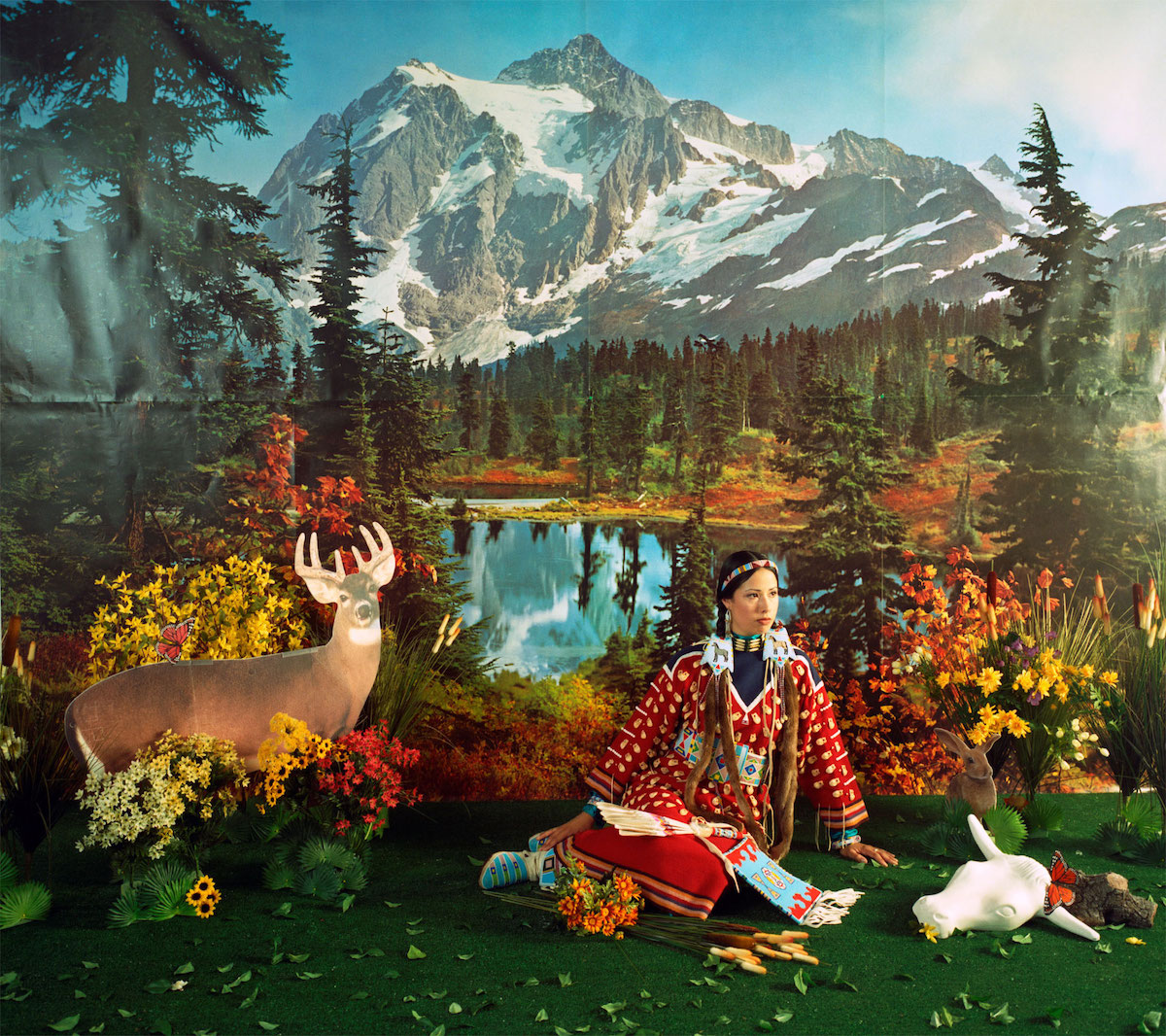 a woman sitting on the ground with the backdrop of a mountain range, a lake and animals