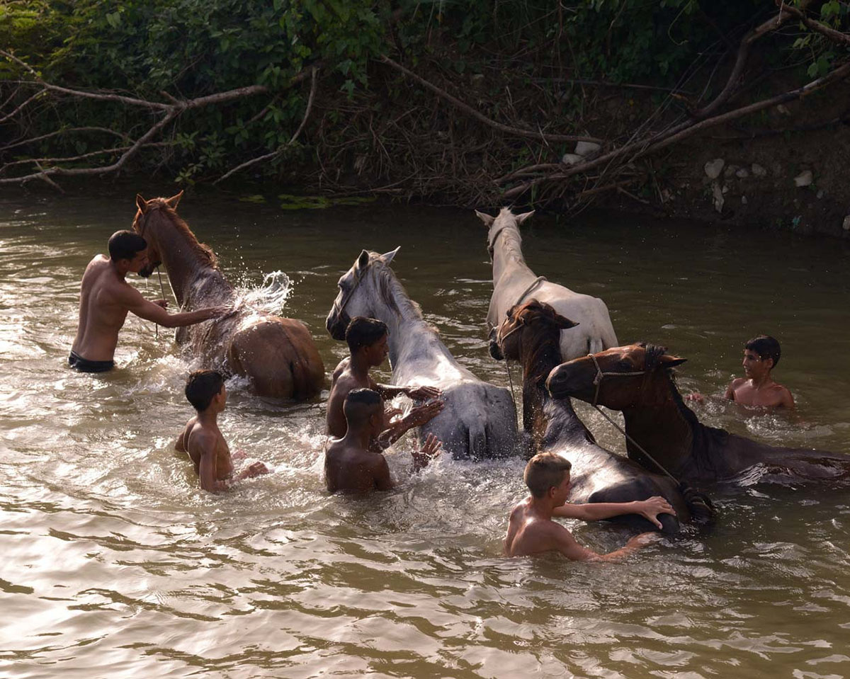 Young campesinos washing their horse before sunset, in the rio La Pastora, close to the city of Trinidad.