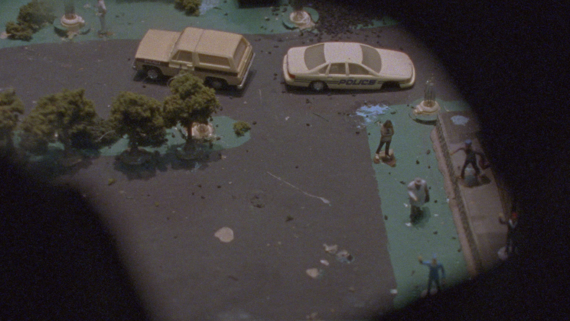 Peep hole showing scale model of a street with police car and human figures in still from Terror Has No Shape(2020) by Luis Arnias