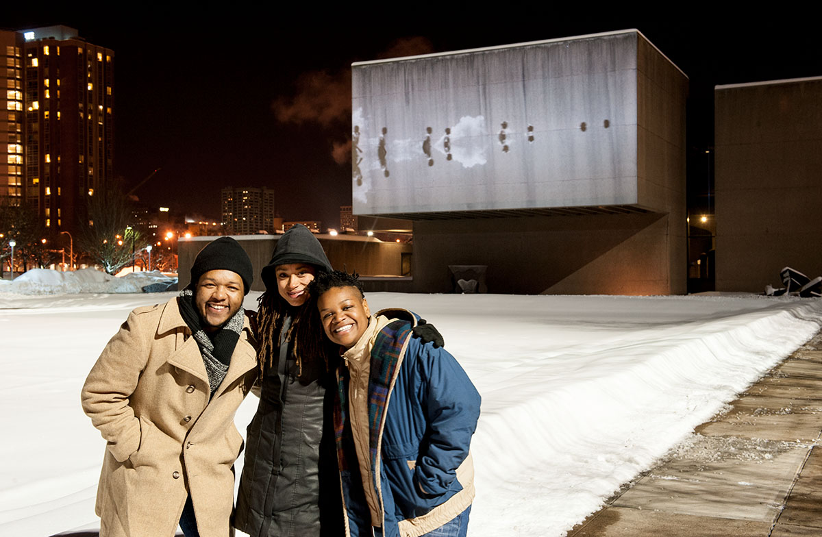 Black Radical Imagination Curators Amir George (left) and Erin Christovale (right) with featured artist Jeannette Ehlers (center) with UVP Everson projection of Ehlers' </em>Black Bullets</em>.