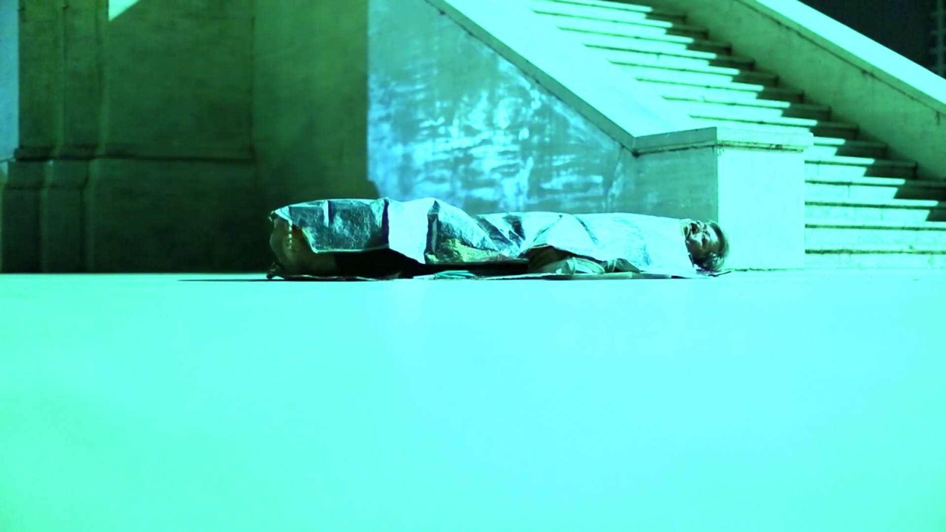 On an empty street bathed in green light, a man lies on the ground under a reflective emergency blanket in still from Blue and Red (2014) by Zhou Tao